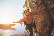 Female rock climber reaching for helping hand - CAIF20289