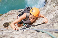 Focused, determined female rock climber scaling rock - CAIF20295