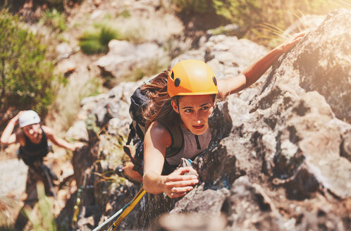 Focused, determined female rock climber hanging from rock - CAIF20298