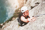 Focused, determined female rock climber scaling rock - CAIF20301