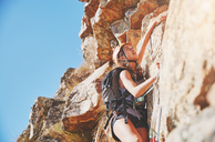 Focused, determined female rock climber scaling rock - CAIF20304