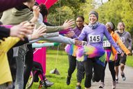 Enthusiastic female runners in tutus high-fiving spectators at charity run in park - CAIF20307