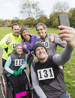 Man in wheelchair taking selfie with friends at charity race in park - CAIF20310