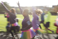 Enthusiastic runners in tutus running at charity run in sunny park - CAIF20316