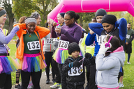 Family and friends with medals at charity run in park - CAIF20322
