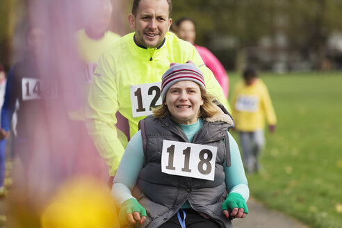 Portrait man pushing smiling woman in wheelchair at charity race in park - CAIF20328