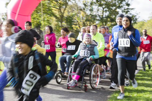 Runners and people in wheelchairs at charity run in park - CAIF20331