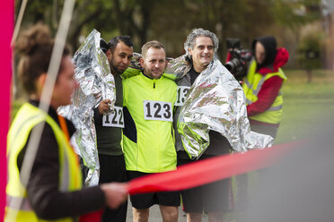 Male marathon runners wrapped in thermal blanket at finish line - CAIF20334