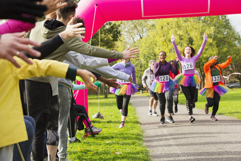 Enthusiastic female runners in tutus nearing finish line at charity run in park - CAIF20340