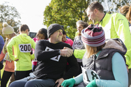 Runner shaking hands with man in wheelchair at charity race in sunny park - CAIF20343