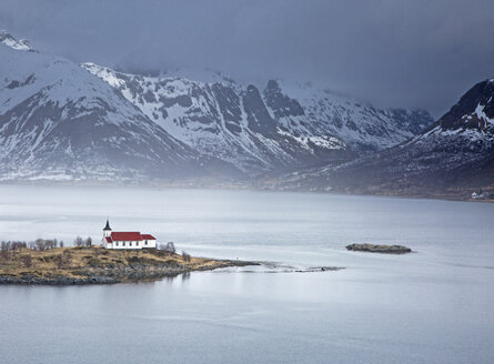 Remote church along fjord waterfront below snowy mountains, Sildpoinesnet, Austvagoya, Norway - CAIF20358