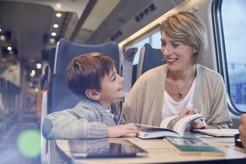 Mother and son reading travel guidebook on passenger train - CAIF20403