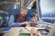 Father and son using smart phone on passenger train - CAIF20406