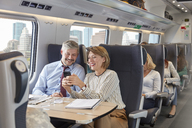 Businessman and businesswoman using smart phone on passenger train - CAIF20409
