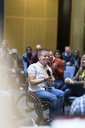 Smiling woman in wheelchair speaking with microphone in audience - CAIF20415