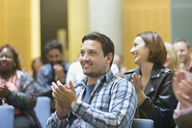Smiling man clapping in conference audience - CAIF20421