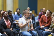 Female speaker in wheelchair with microphone talking to audience - CAIF20439