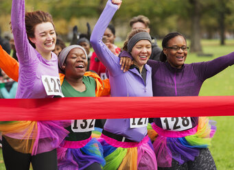Women friend runners in tutus running, crossing charity run finish line - CAIF20457