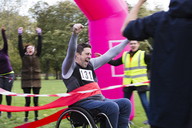 Enthusiastic man in wheelchair crossing charity race finish line - CAIF20460