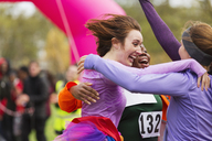 Enthusiastic female runners finishing charity run, celebrating - CAIF20463