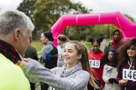 Daughter placing medal around neck of father at charity run - CAIF20466