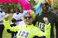 Portrait enthusiastic male runners wearing wigs at charity run - CAIF20469