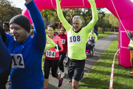 Enthusiastic runners cheering, crossing charity run finish line - CAIF20472