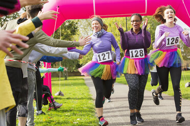 Spectators high-fiving female runners in tutus crossing charity run finish line - CAIF20478