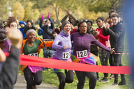 Enthusiastic female runners in tutus nearing finish line at charity run - CAIF20481