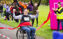 Enthusiastic man in wheelchair crossing finish line at charity race in park - CAIF20484