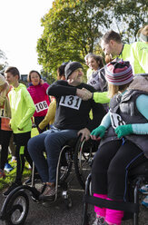 Man in wheelchair shaking hands with runner in crowd at charity race - CAIF20493