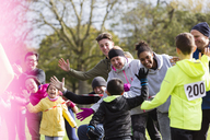 Spectators high-fiving runners at charity run in park - CAIF20499