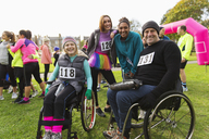 Portrait smiling friends in wheelchairs at charity race in park - CAIF20502