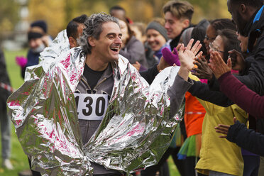 Enthusiastic male marathon runner in thermal blanket high-fiving spectators - CAIF20505