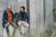 Confident senior man and young man sitting in the city talking - GUSF00642