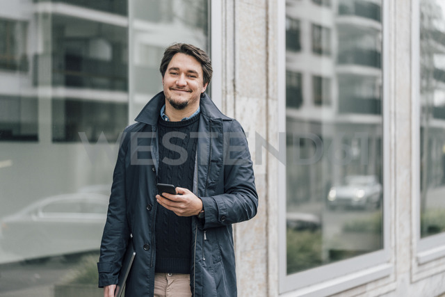 Portrait of smiling young man with cell phone in the city - GUSF00645