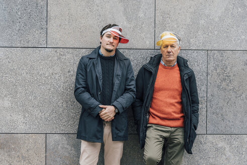 Portrait of young man and senior man wearing sun visors leaning against a wall - GUSF00654