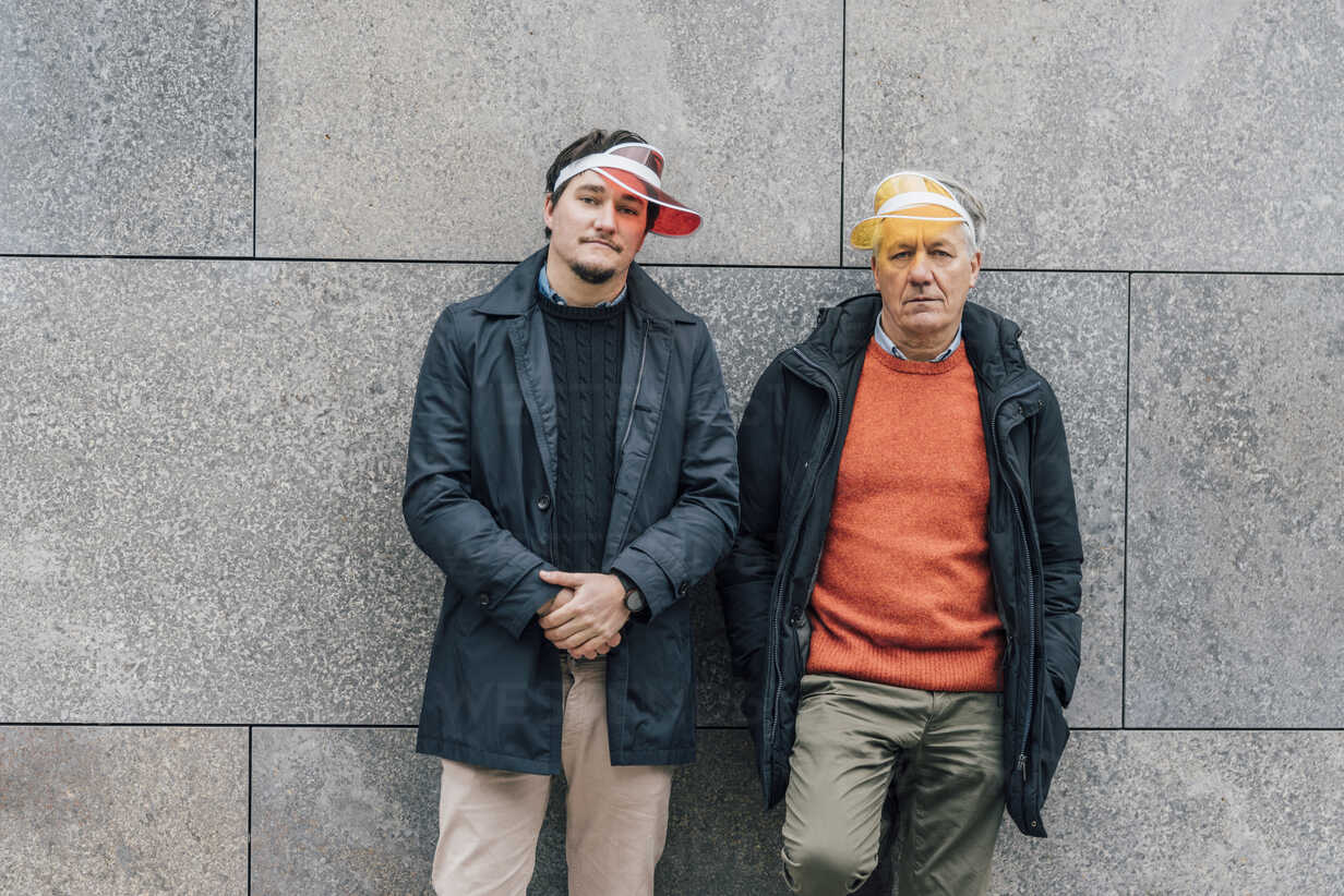 Portrait of young man and senior man wearing sun visors leaning against a wall - GUSF00654 - Gustafsson/Westend61