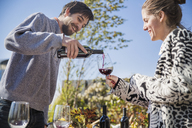 Low angle view of man pouring red wine for female friend during garden party - CAVF48230