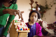 Girl looking at mother decorating gingerbread house at home - CAVF48293