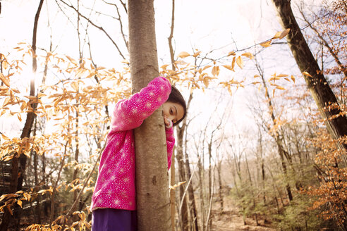 Portrait of girl embracing tree trunk at yard during autumn - CAVF48296