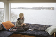 Thoughtful woman having coffee while looking at lake through window during winter - CAVF48353