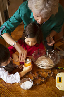 High angle view of grandmother with kids preparing cookies at home - CAVF48602