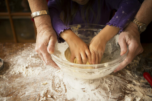 Cropped image of girl with grandmother kneading dough while preparing cookies - CAVF48608