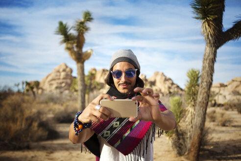 Man taking selfie while standing in desert area - CAVF48683