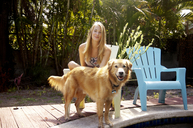 Portrait of woman with golden retriever sitting on chair at poolside - CAVF48722