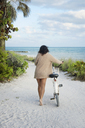 Rear view of woman with bicycle walking on sand against sea - CAVF48728