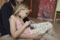 Mother and daughter, playing with toy car - KMKF00233