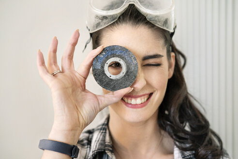 Young woman renovating her new flat, looking through grinding disc - PESF01039