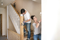 Young couple refurbishing new home, painting staircase - PESF01063